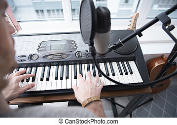 Young man performing music on synthesizer - Top view close...
