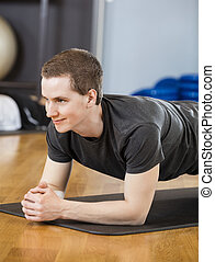 Young Man Performing Plank Position In Gym