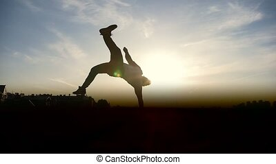 Young man performing somersault in front of the sun,...