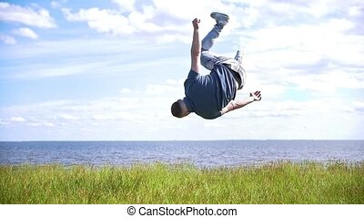 Young man performs acrobatic stunts on the hill on background of river