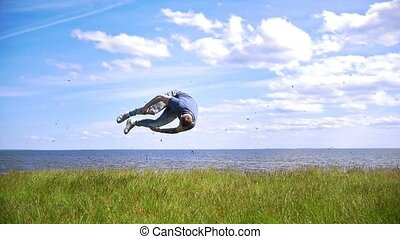 Young man performs flips on the green hill on background flock of swallows flying over the river