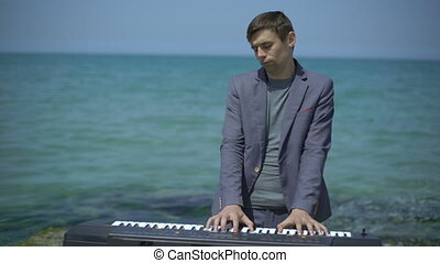 Young man performs witm synthesizer on azure coast, beach or...