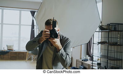 Young man photographer working in a photo studio taking...
