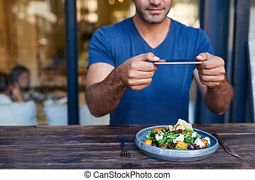 Young man photographing his salad at a bistro table - Young...