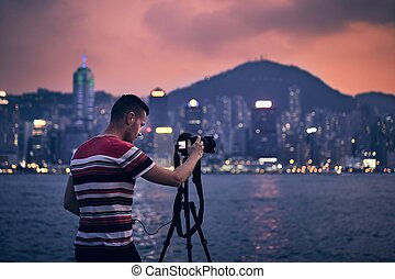 Young man photographing urban skyline - Young photographer...