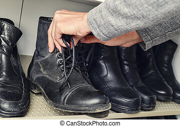 young man picking a pair of boots from the closet