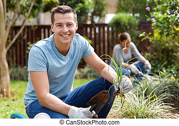 young man planting with his wife