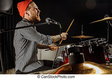 talented young caucasian man contemporaneously play on drums and sing on microphone. professional drummer preparing for rock concert, practice in dark studio. music concept