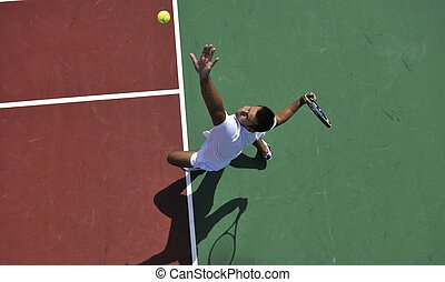 young man play tennis outdoor on orange tennis field at...