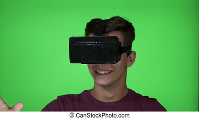 Young man playing a horror adventure game using a VR virtual...