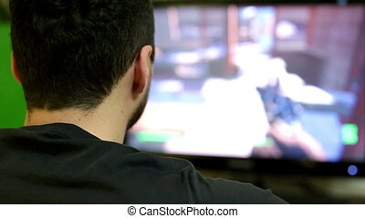 Young man playing a video game on personal computer