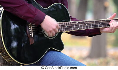 Close up man's hands playing acoustic guitar artist musician outdoors.