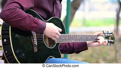 Young man playing acoustic guitar outdoors - Close up person...