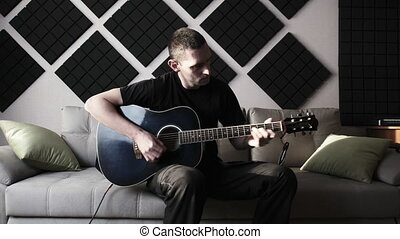Young man playing acoustic guitar while sitting on sofa in home recording studio. Recording an electric acoustic guitar at home. A guy in a stylish room made of acoustic foam. Blogger teaches to play