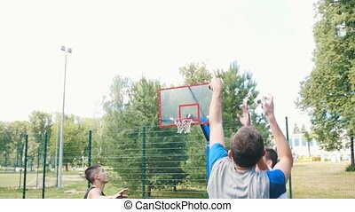 Young man playing basketball on the court outdoors with friends, throwing the ball and missing the basket