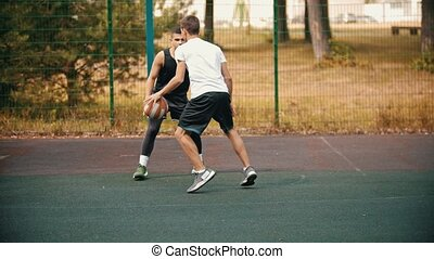 Young man playing basketball on the sports ground with...