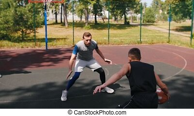 Young man playing basketball outdoors with friends and...