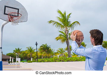 Young man playing basketball outside at exotic resort