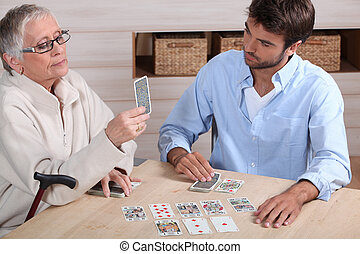 young man playing cards with older woman