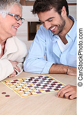 young man playing checkers with older woman