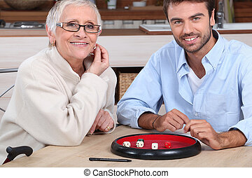 young man playing dice with older woman