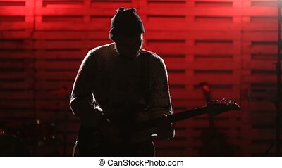 Young man playing electric guitar on stage - Stylish...