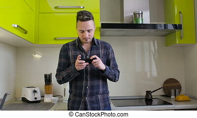 Young man playing game on smartphone standing in kitchen at home