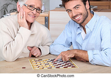 Young man playing game with elderly woman