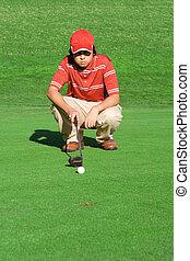 young man playing golf calculating shot