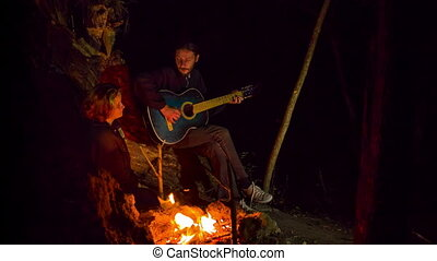 Young Man Playing Guitar And Singing A Song To A Girl At Bonfire