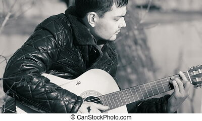 Young man playing guitar near the river (b&w)