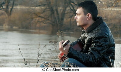 Young man playing guitar near the river (retro)