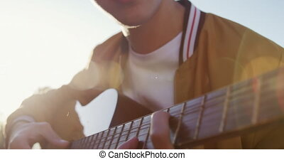Young man playing guitar on a rooftop with his friends - ...