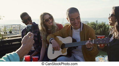 Young man playing guitar on a rooftop with his friends