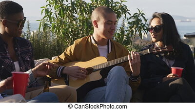 Multi-ethnic group of friends hanging out on a roof terrace together, Caucasian man is playing guitar, drinking drinks from red cups, drinking beer, in slow motion