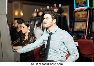 Young man playing in slot machines - Good looking young...