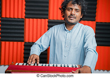 Young man playing Indian music instrument Harmonium in recording studio - Concept of hobby and leisure activities.