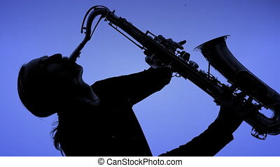 Young man playing sax in the dark. Close-up