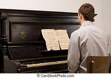 Young man playing sheet music on a piano