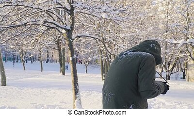 Young man playing snowballs in the park 4K