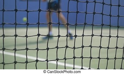 Young man playing Tennis with tennis Racket on a sunny day. slow motion. blurred on grid foreground.