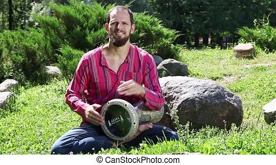 Young man playing the drum outdoors - Young man playing the...
