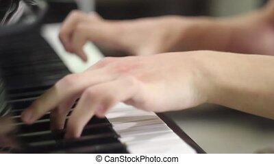 young man playing the piano. hands close up. exercises on the musical instrument. keyboard musical instrument. salfegio. long fingers of a musician. musical education in school.