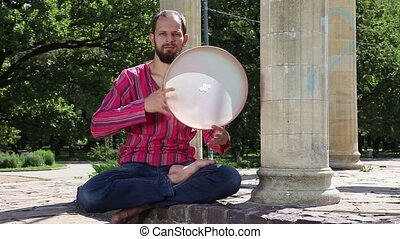 Young man playing the tambourine ou - Young man playing the ...