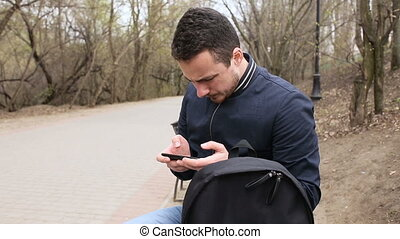 Young man playing touch screen phone in the park
