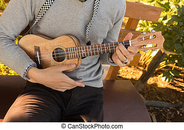 Young man playing ukulele.