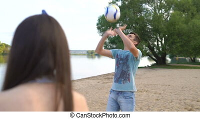 Young man playing volleyball on a sandy beach near a lake....