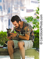 Young Man Playing With A Cat In Public Park