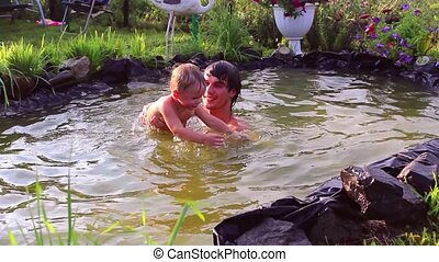 young man playing with a small child in the pond