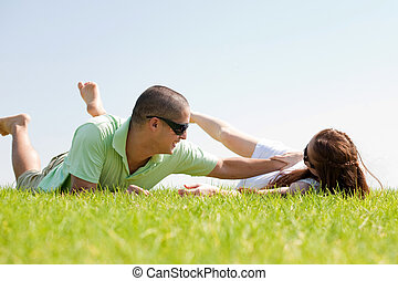 Young man playing with his wife on a grass